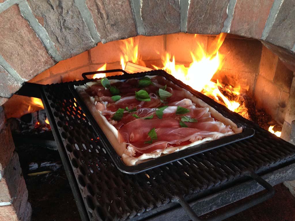 Pizzu pečeme na mírnějším ohni, přímo pod plechem by pak měly být jen uhlíky (i my jsme u první pizzy z obrázku ještě měli počkat).