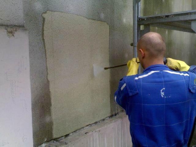 Muž kolem 40 let v pracovním oděvu čistí fasádu vysokotlakým čističem