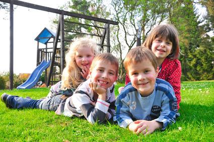 Čtyři smějcí se děti, v pozadí dětské hřiště