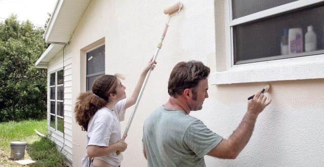 Muž (se štetcem) a dívka (s válečkem) natírají bílý dům ochranným nátěrem