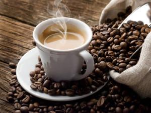 Šálek kávy mezi praženými zrny
