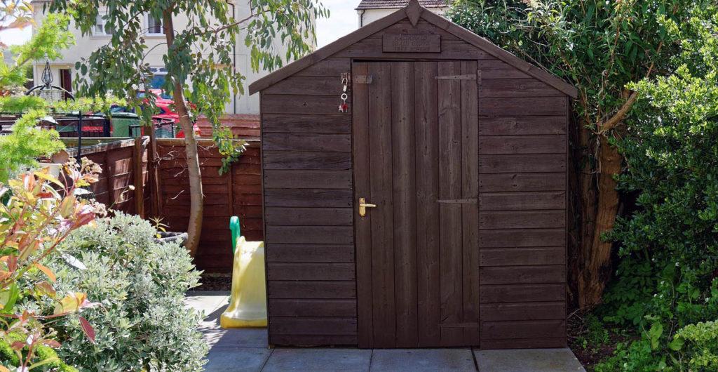 Dřevěný zahradní domek s tmavým nátěrem a dveřmi klasických rozměrů